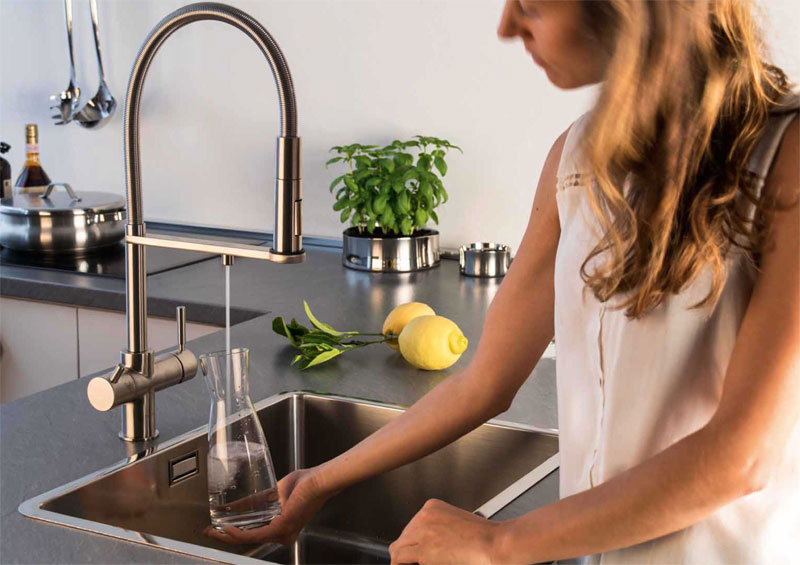 Kühles sprudelwasser wird in der küche aus der einhandmischarmatur in eine kraffe gezapft