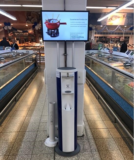 Kunden erfrischen sich am Infocooler und verfolgen Angebote am Monitor